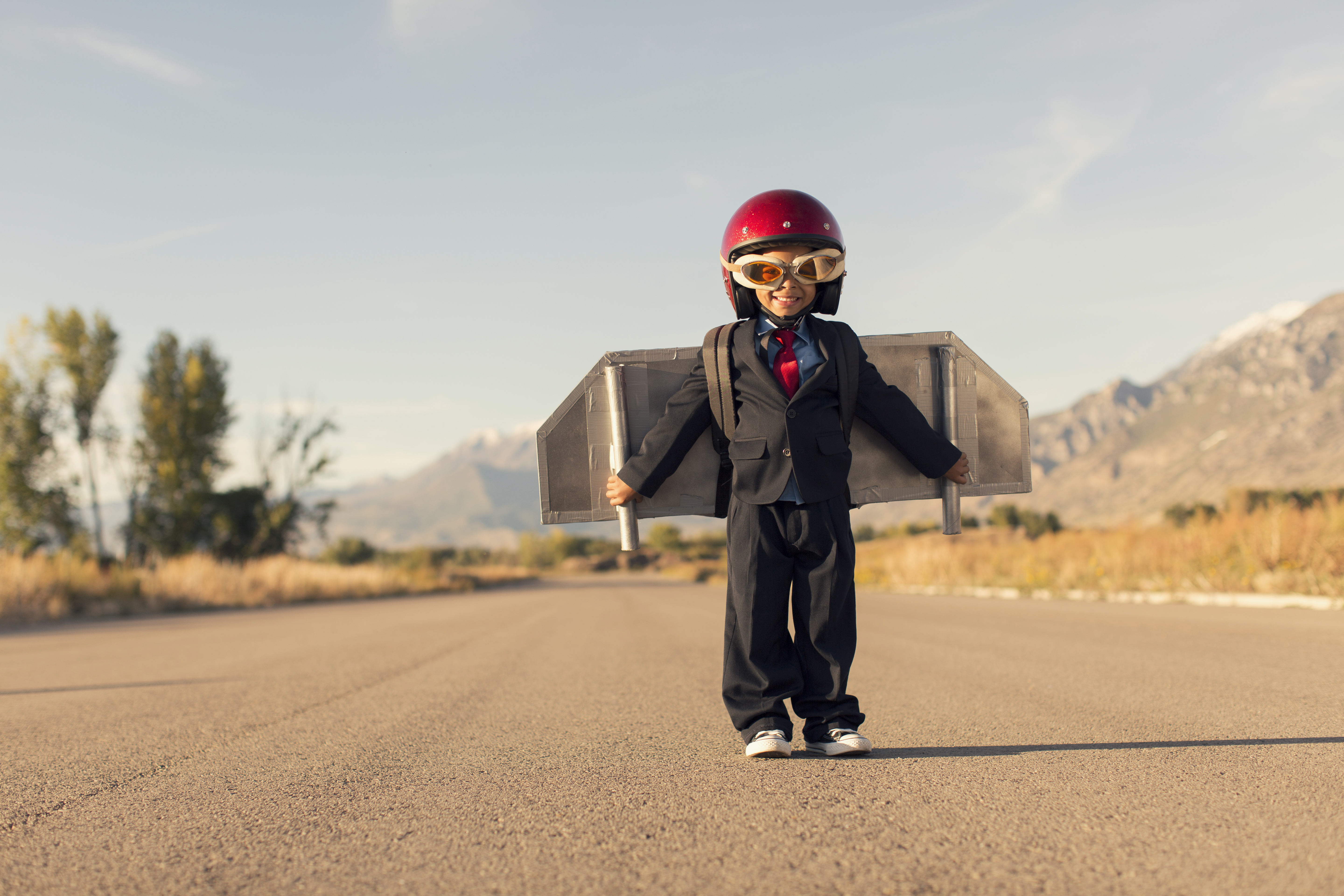 A young business boy is ready to take his business ideas to new levels in the stratosphere. He is wearing a homemade jet pack, race helmet and flying goggles while standing on a rural road in Utah, USA.