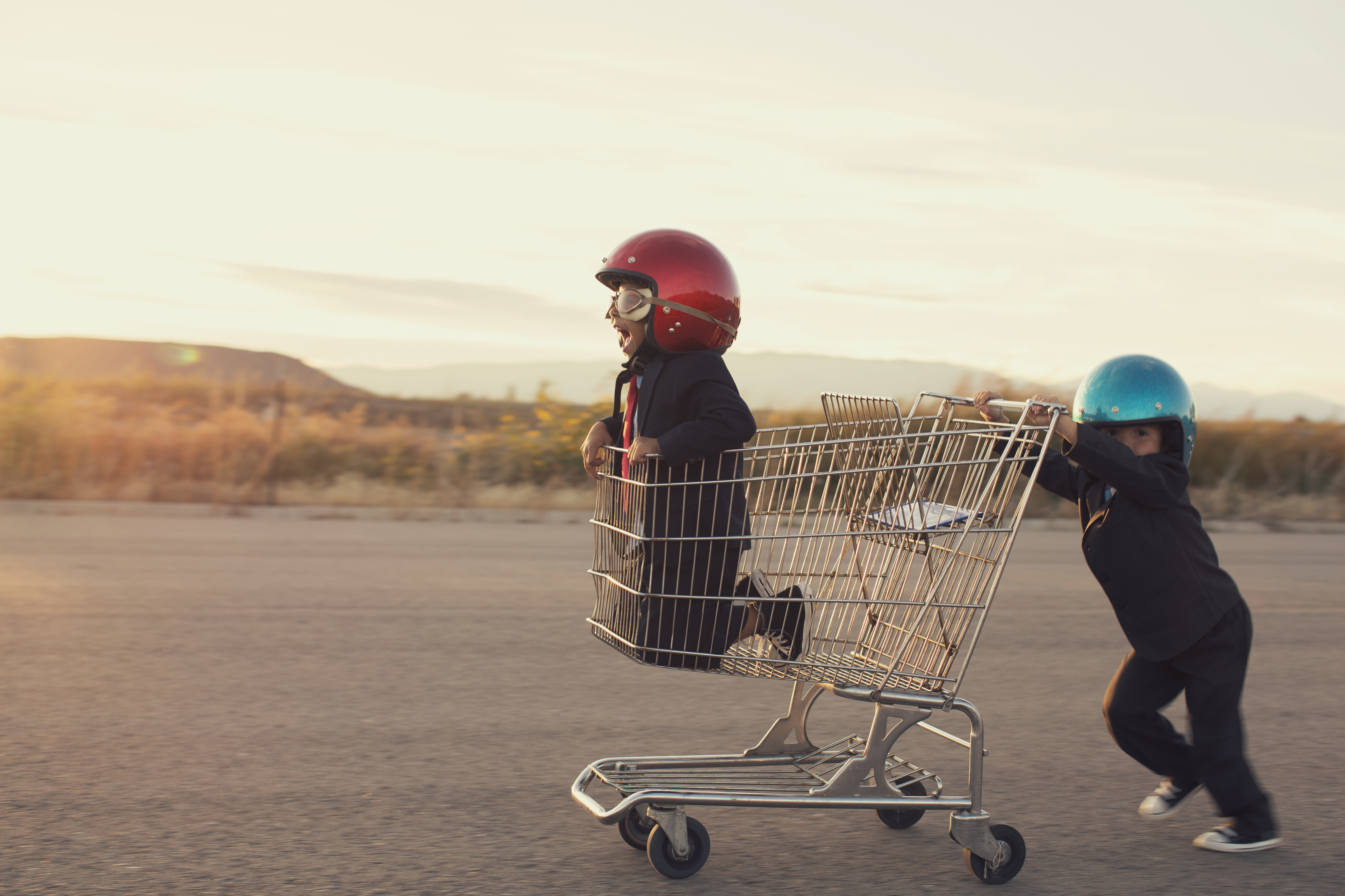 Young businessmen and boys dressed in business suits and racing helmets are ready to race their business to new levels. Boys race in a shopping cart in a Utah valley.
